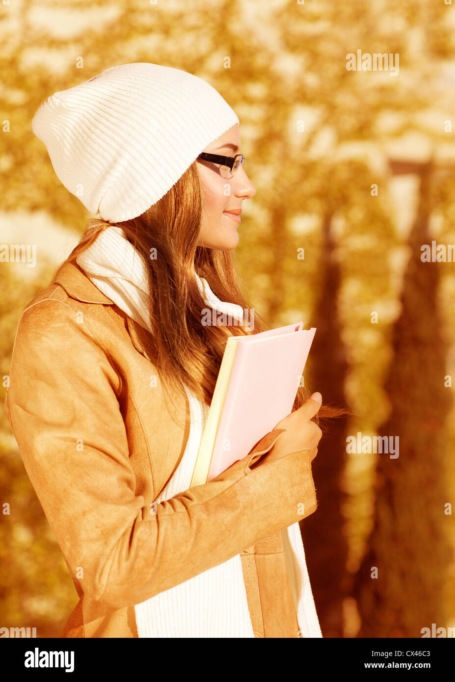 Photo of pretty student girl standing in autumn park and wearing beige leather coat with white warm hat, cute schoolgirl - Stock Image