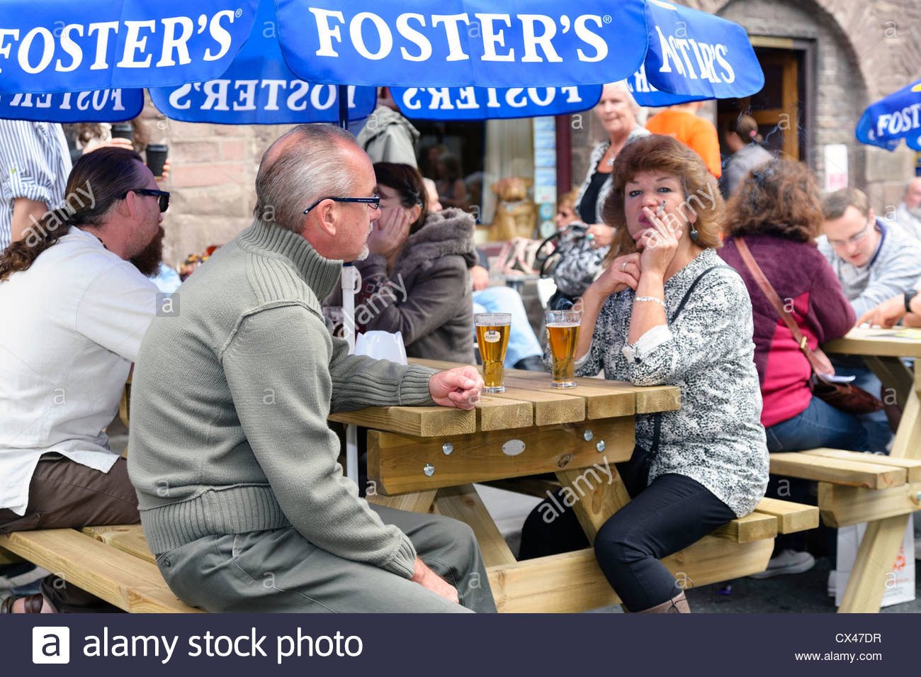 Woman smoking a cigarette in a pub beer garden, Abergavenny, Wales, UK. - Stock Image