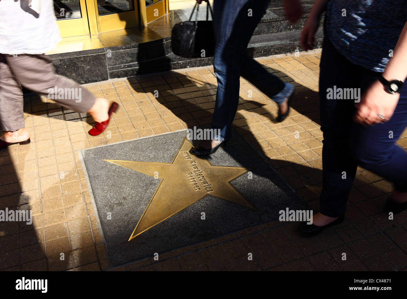 Women walking by Jerzy Kawalerowicz star in Lodz walk of fame at Piotrkowska street, Poland - Stock Image