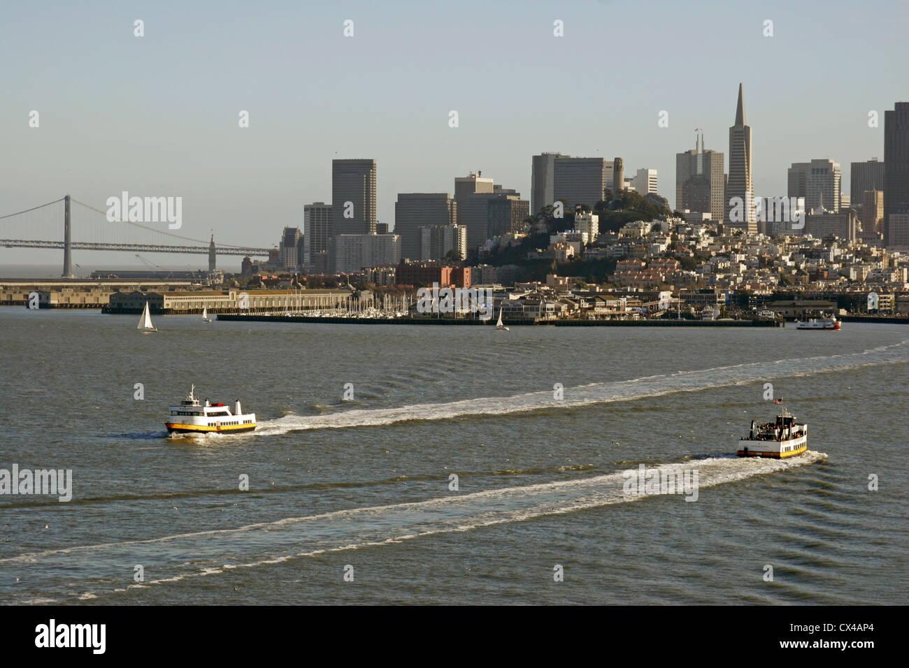 Ferries cross between Alcatraz Island and San Francisco's waterfront. California, USA. - Stock Image