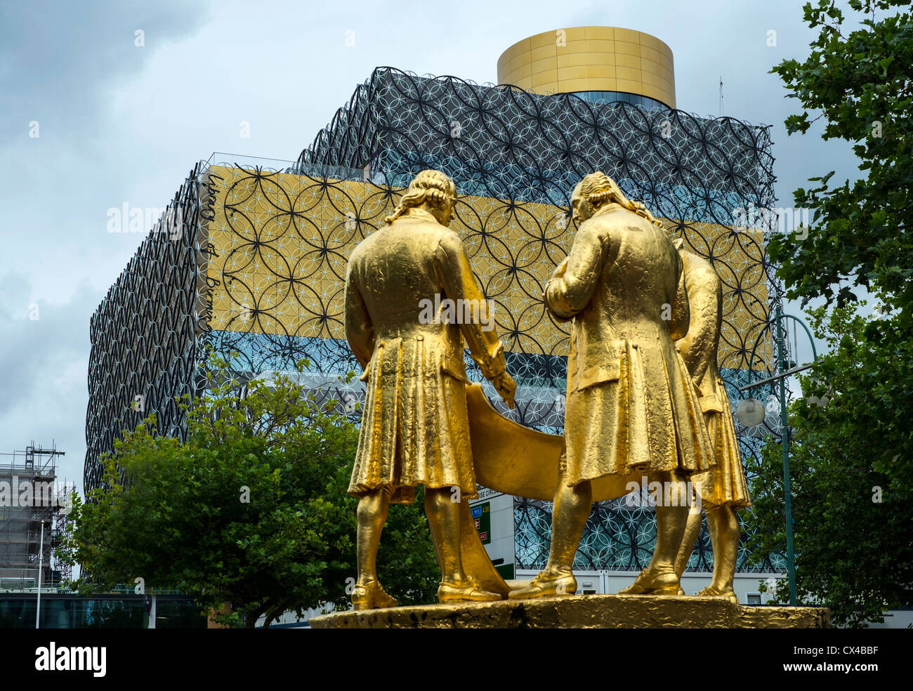 The three guilded figures of Watt, Boulton and Murdoch stand facing the new Library of Birmingham. - Stock Image
