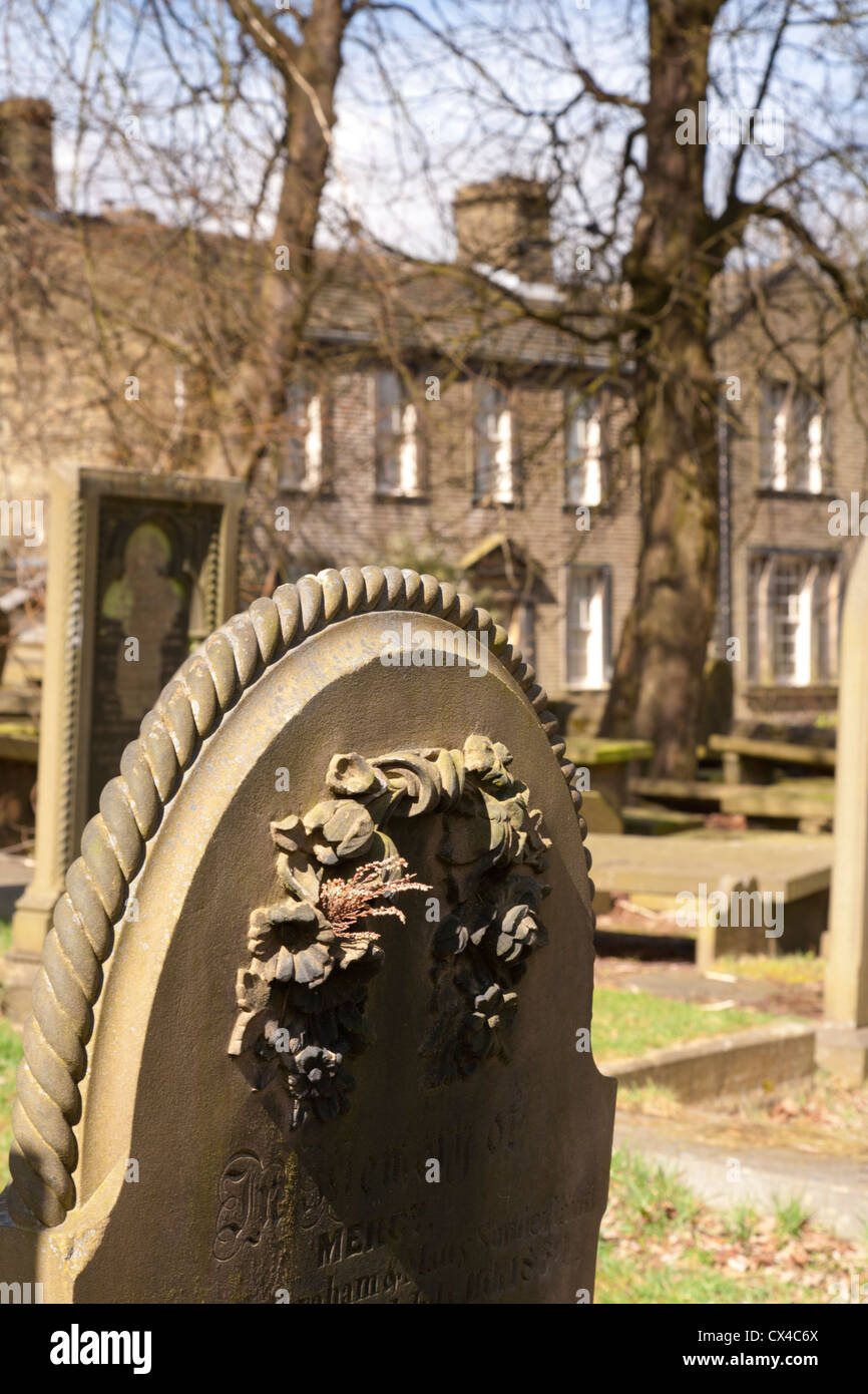 Gravestone in Haworth cemetery, and the Bronte house behind. Focus on gravestone. - Stock Image