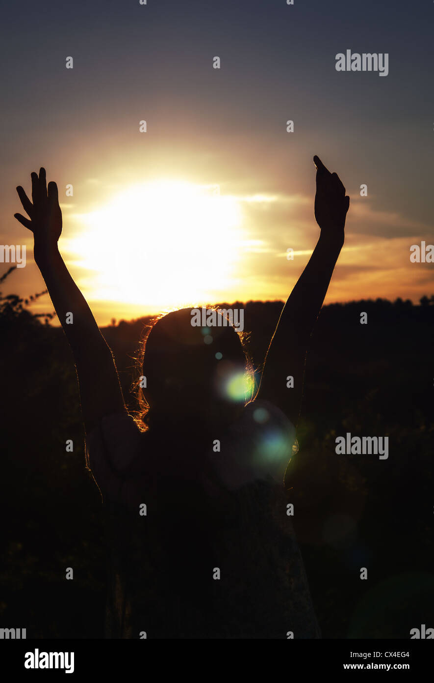 Young girl with hands up surrounding the sun at sunset - Stock Image