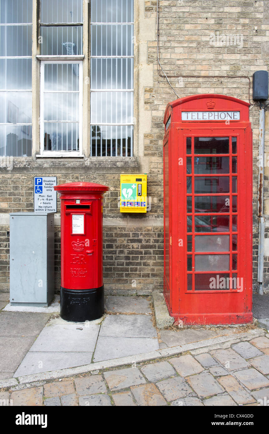 An Automated External Defibrillator between a Royal Mail post box and British Telecom public telephone kiosk in - Stock Image