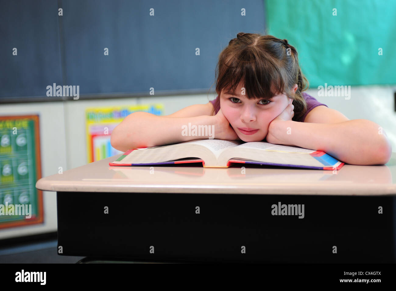 USA A third 3rd grade girl sits bored in a classroom at her public school - Stock Image