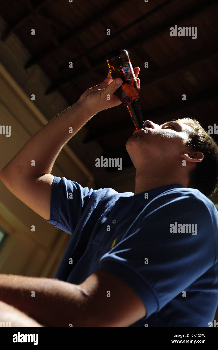Teenage boy drinking beer in a basement of a house - underage under age illegal wasted youth - Stock Image