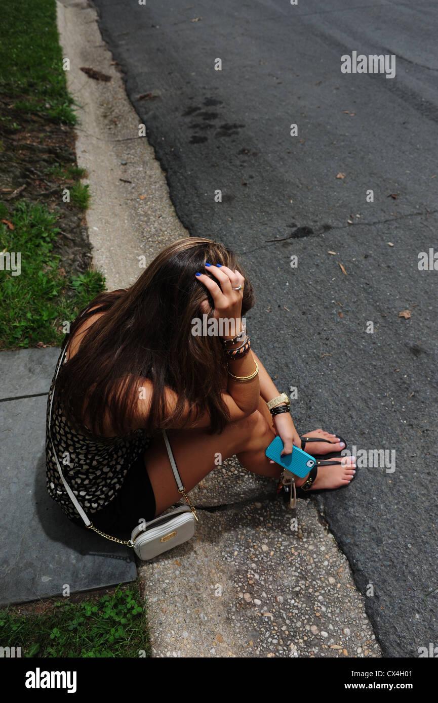 Teenage girl sitting on the curb of a street - upset depressed sad underage drinking - Stock Image