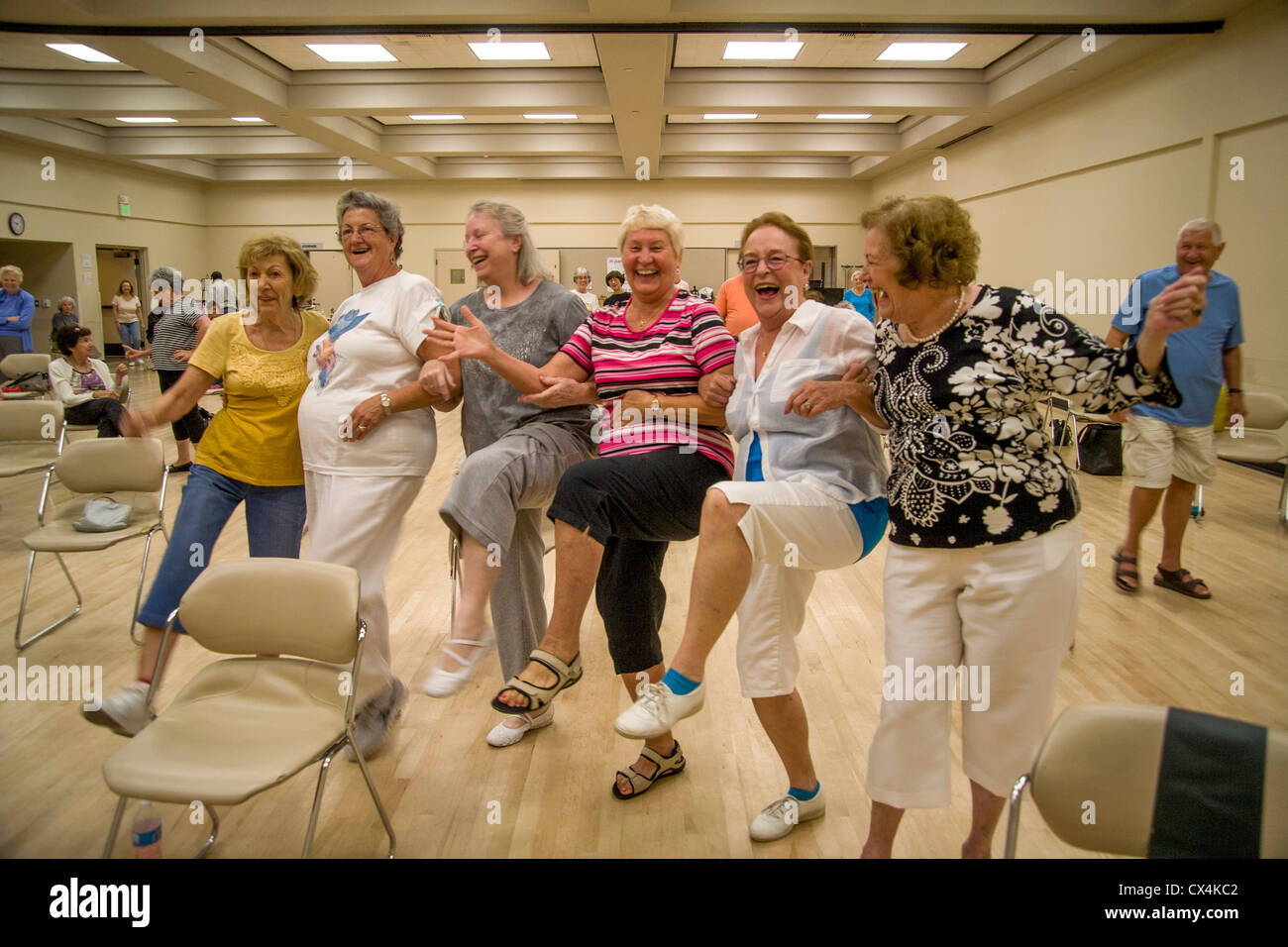 Exuberant senior women form a spontaneous kick line before a chair exercise class at a senior center in Tustin, - Stock Image