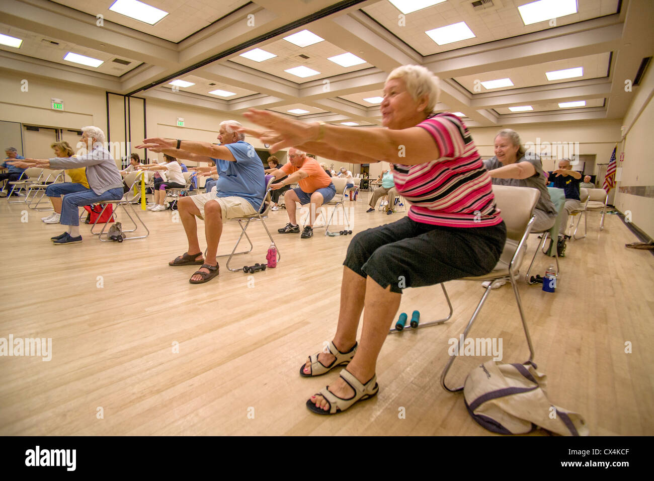 Senior women and men work out during a chair exercise class