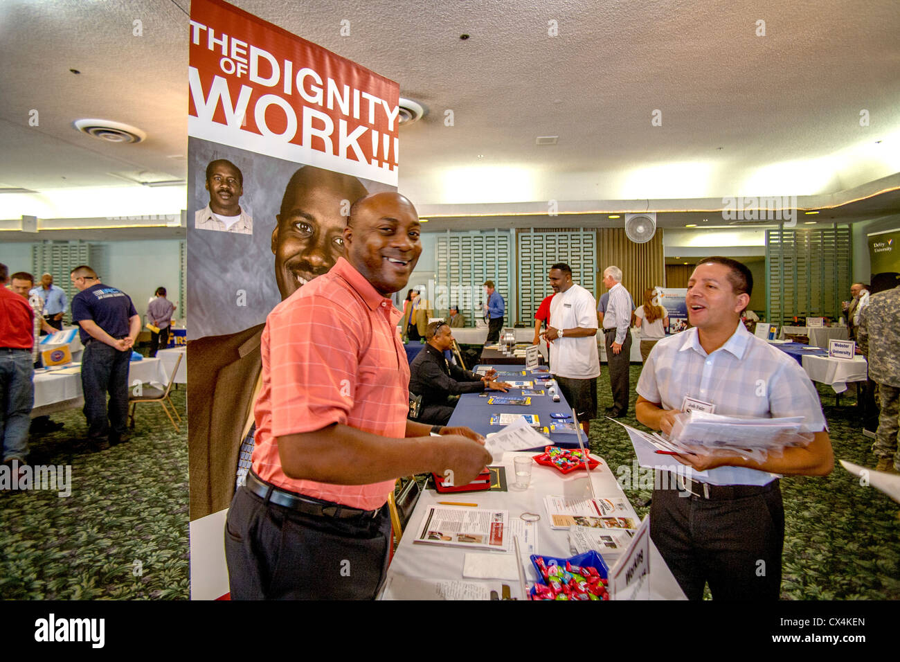 A jolly African American reminds job seekers of the dignity of work at a job fair for military veterans in Santa - Stock Image