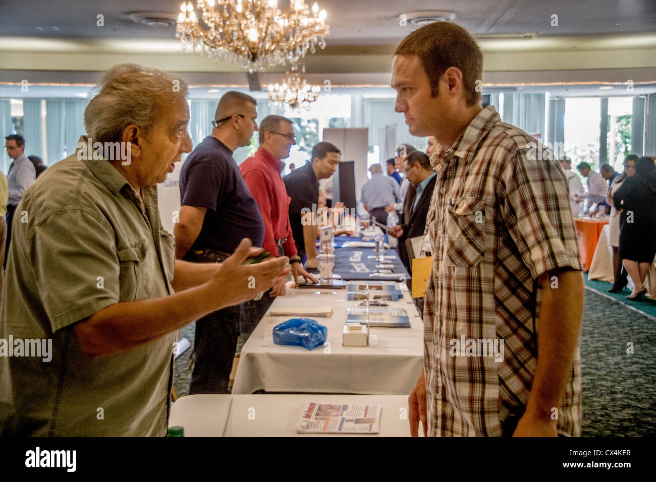 A young man discusses employment possibilities at a job fair for military veterans in Santa Ana, CA. - Stock Image