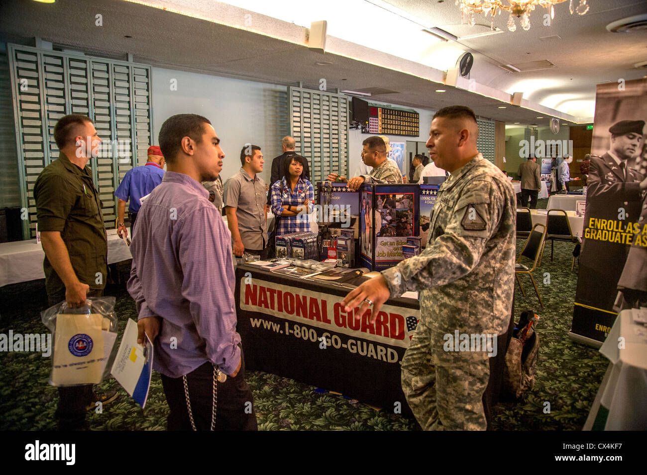 A young Hispanic man talks with a U.S. Army National Guard recruiter at a job fair for military veterans in Santa - Stock Image
