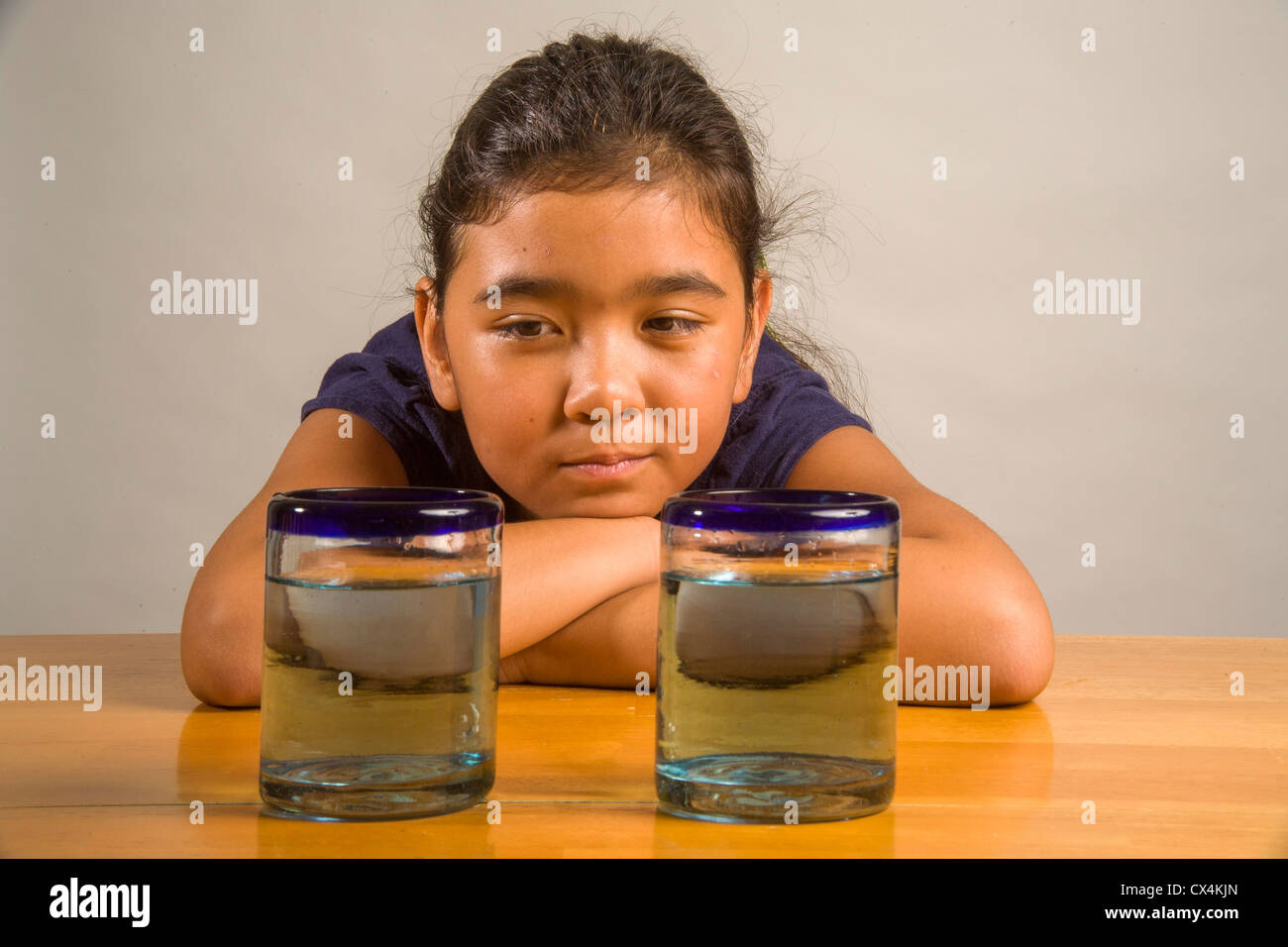 A child looks at identical glasses filled with the same amount of liquid to demonstrate Piaget's Liquid Conservation - Stock Image