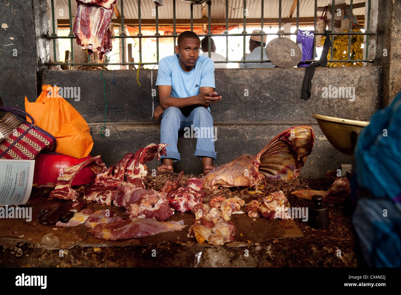 Butcher with meat for sale in the indoor food market, Darajani market, Stone Town, Zanzibar, Africa - Stock Image