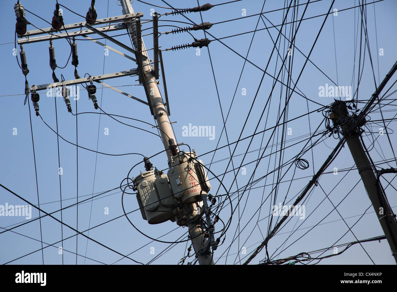 A tangle of electrical power lines overhead - Stock Image