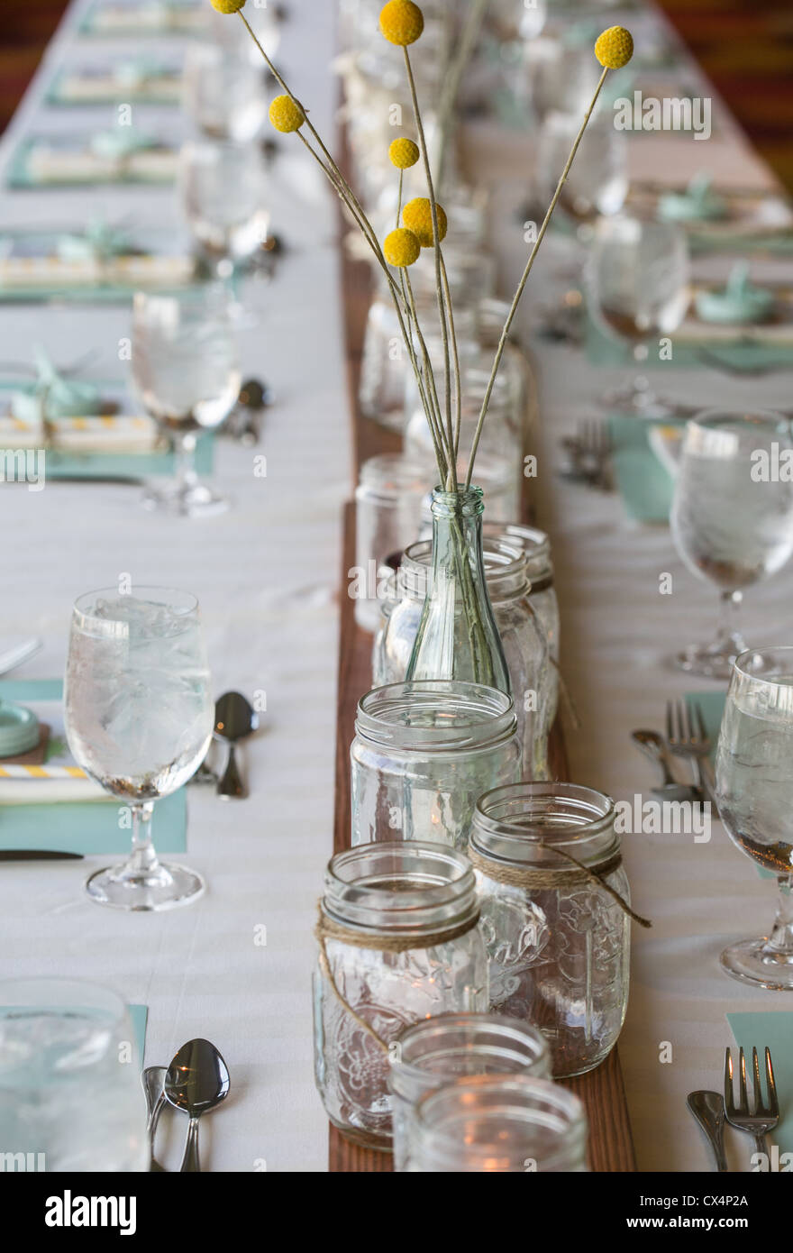 Rustic table setting for a wedding featuring mason jars glass bottles holding Craspedia (Billyu0027s Balls) flowers & Rustic table setting for a wedding featuring mason jars glass ...