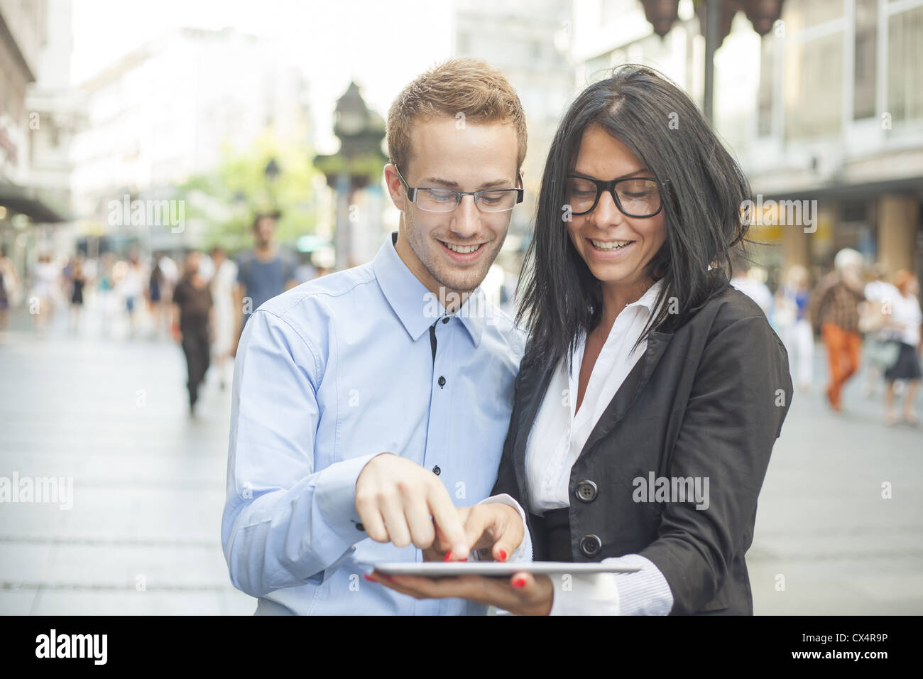 Two businesspeople on street with tablet computer - Stock Image