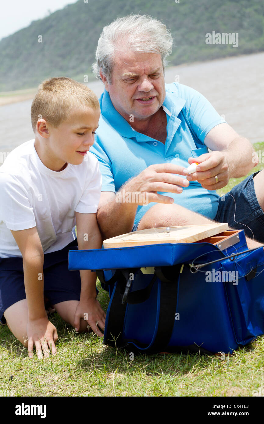 grandfather teaching grandson how to prepare fishing tackles - Stock Image
