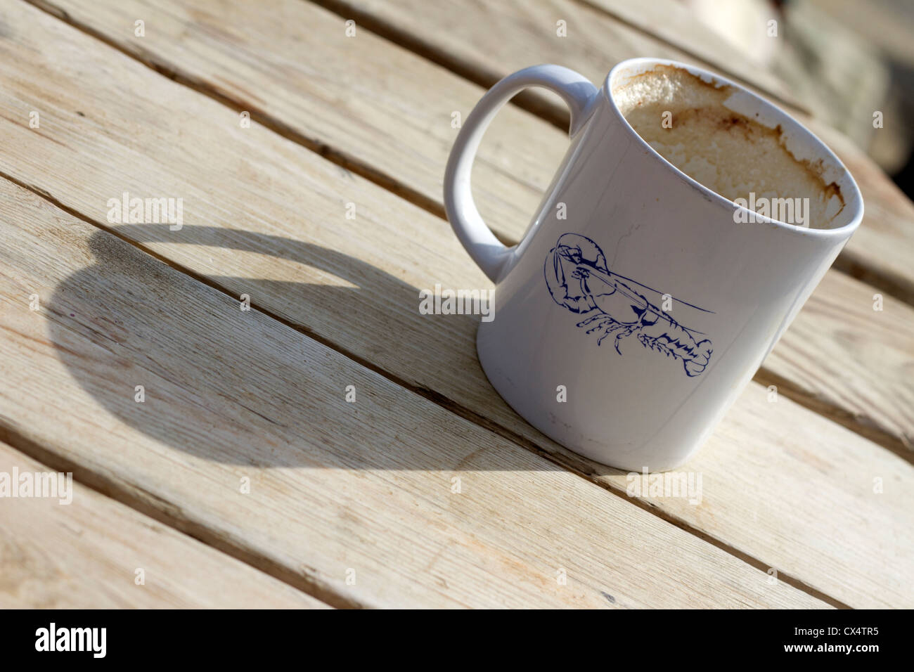 A used mug on a wooden table. - Stock Image