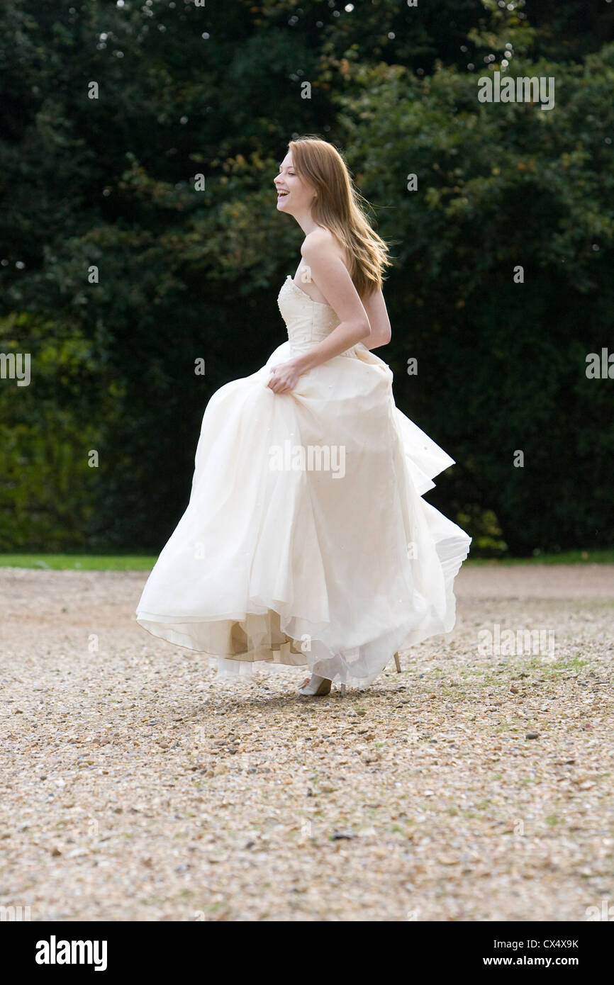 Side view of young woman in cream bridal dress holding skirts in grounds of stately home - Stock Image