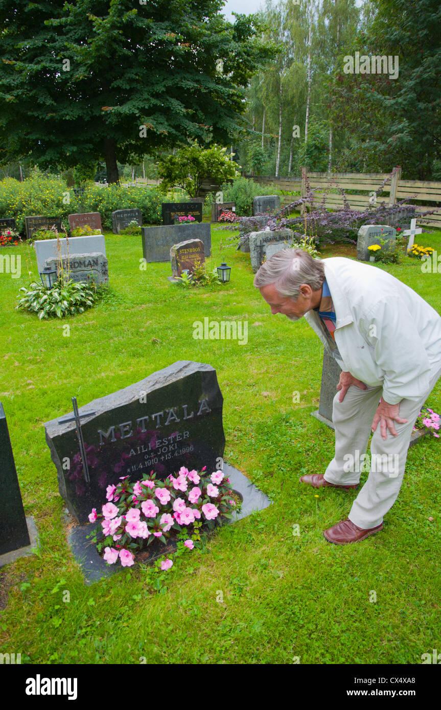 Man in his 70s by the graveside of a relative at graveyard in Reposaari island Pori city Satakunta county western - Stock Image