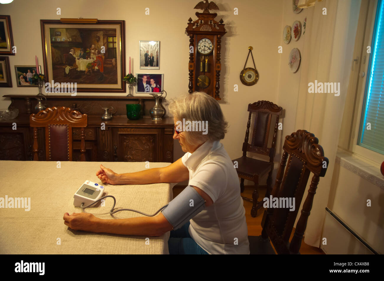 Woman in her early 70s using blood pressure monitor Finland Europe - Stock Image