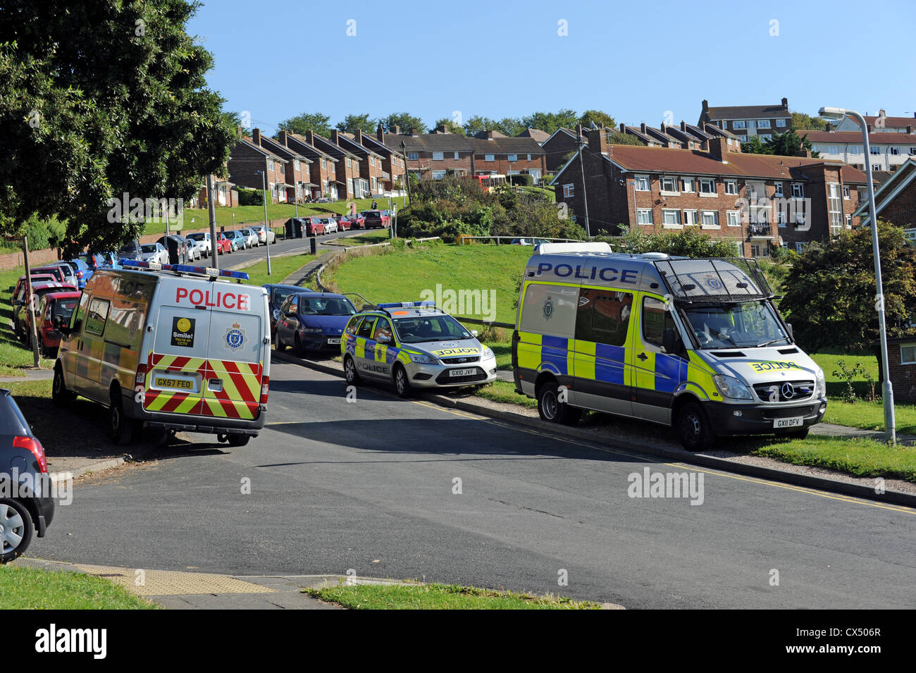 Police cars and vans parked up on a housing estate in Brighton while the Police carry out a drugs raid - Stock Image