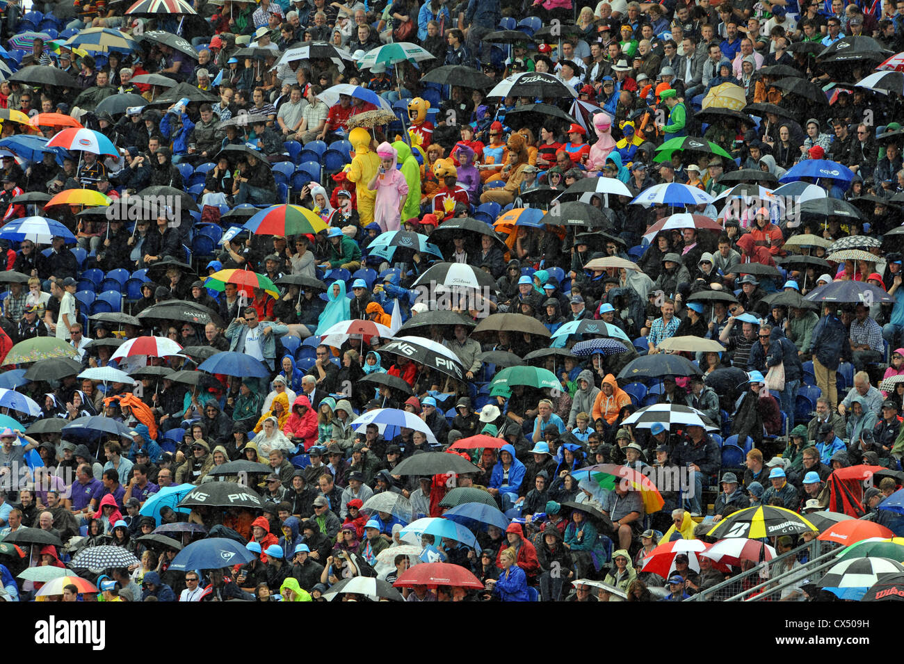 Umbrellas come out as heavy rain starts during the cricket Twenty20 Finals Day 2012 at the Swalec Stadium in Cardiff - Stock Image