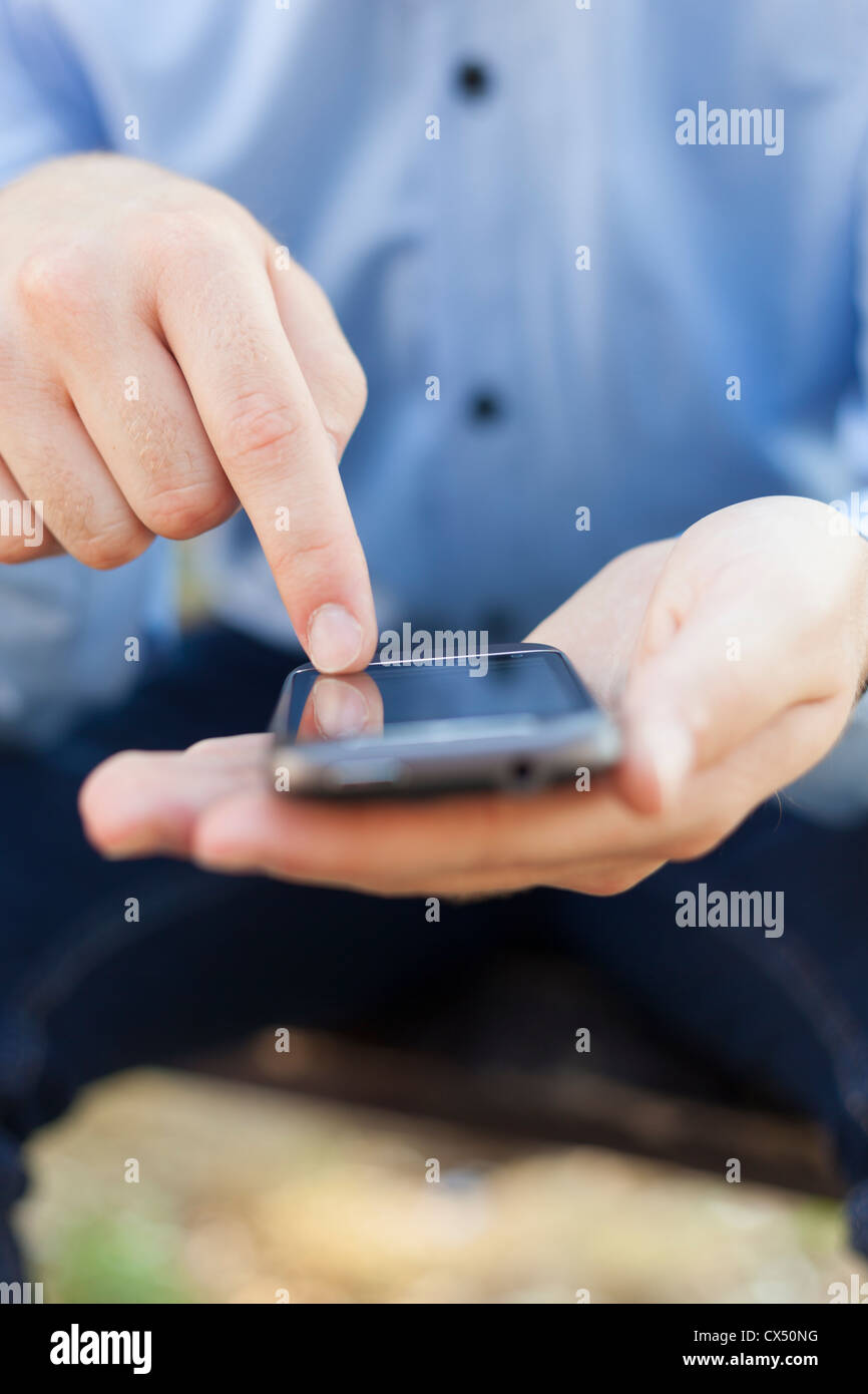 Man with smart phone on hand, blurred background - Stock Image