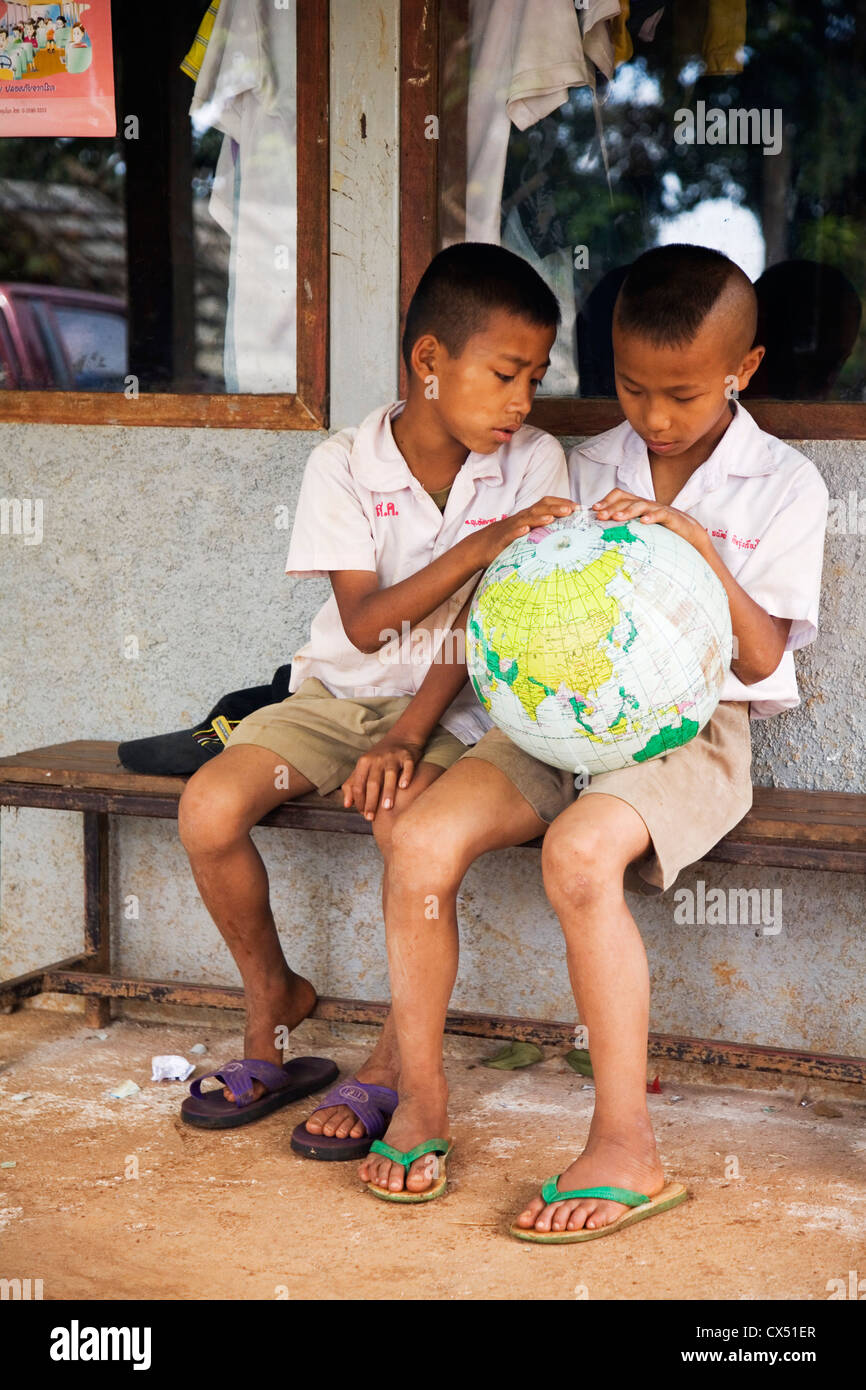 Thai schoolchildren studying a world globe. Mae Hong Son, Mae Hong Son, Thailand - Stock Image