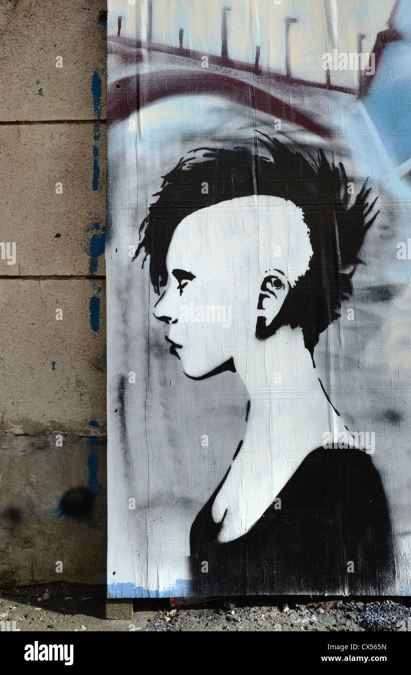 Stencil graffiti featuring a female punk in profile on boards in New Street, Edinburgh Scotland, UK. - Stock Image