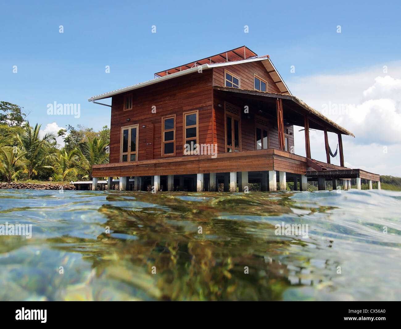Tropical stilt house over the caribbean sea stock photo for Stilt home builders