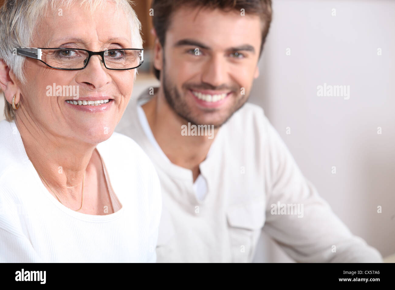 Senior woman sitting with a young man - Stock Image