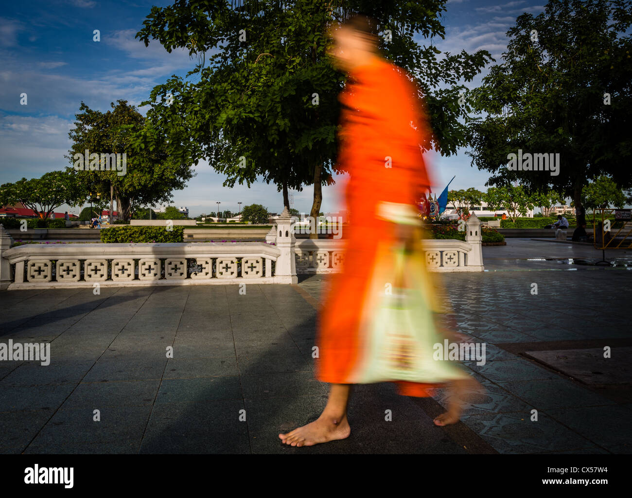 Blurred photo of Buddhist monk walking in the streets of Bangkok, Thailand - Stock Image