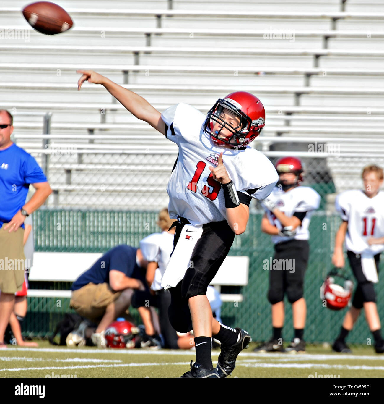 Youth football player throwing a pass. - Stock Image