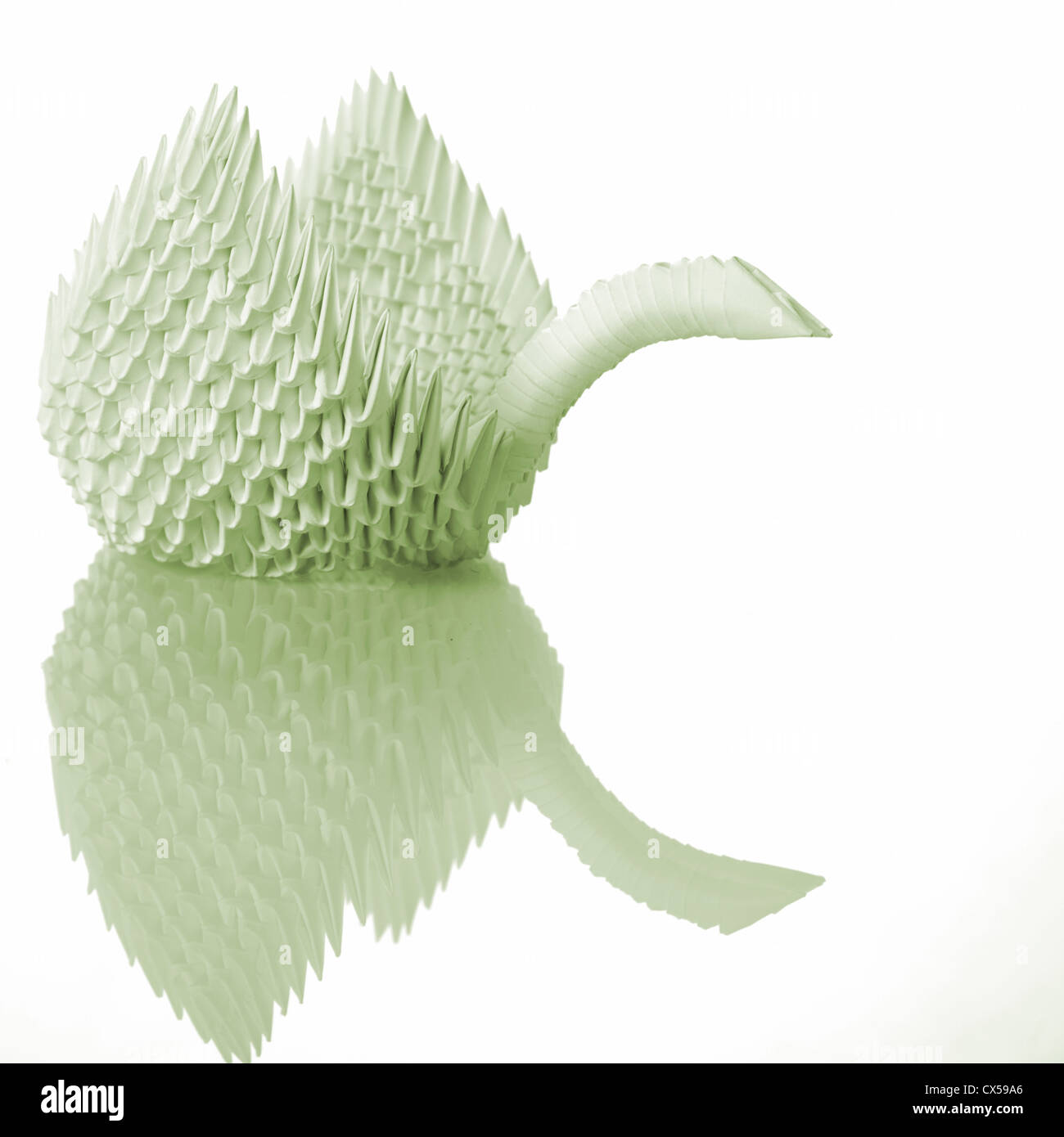 Origami art swan on table with reflection - Stock Image