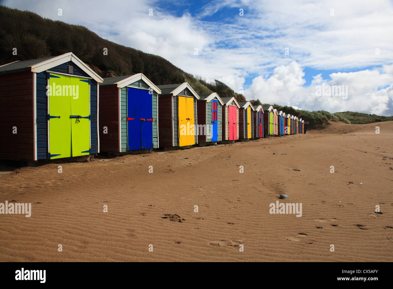 Row of brightly colored beach huts on sand beach blue sky with white clouds - Stock Image