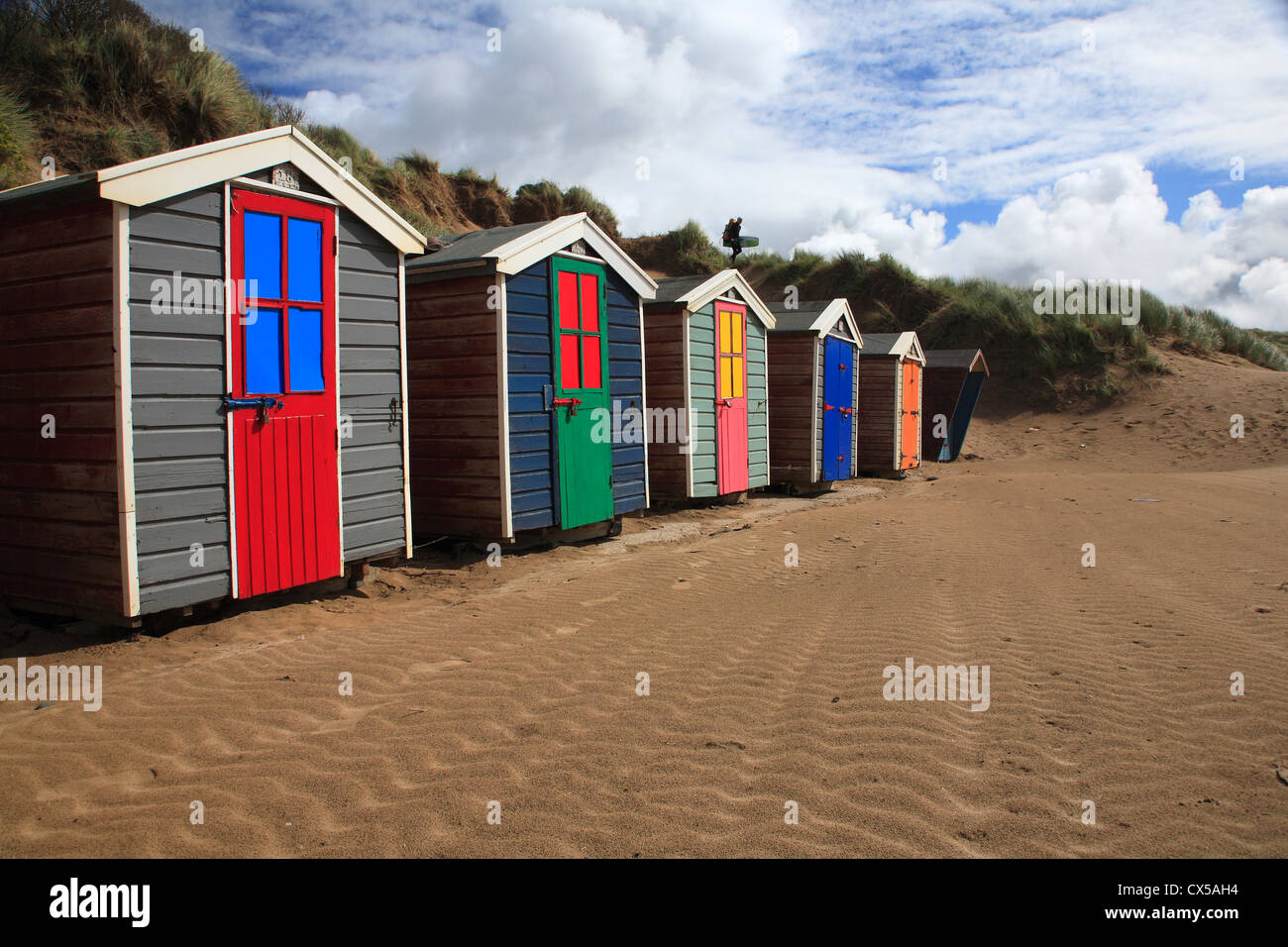 Brightly coloured beach huts with surfer silhouetted on horizon - Stock Image