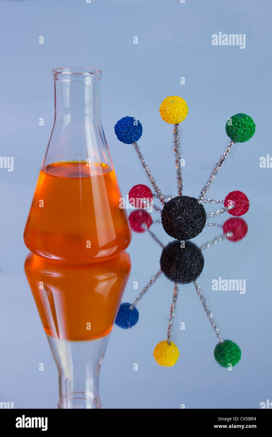 orange chemistry flask with molecular model and reflections - Stock Image