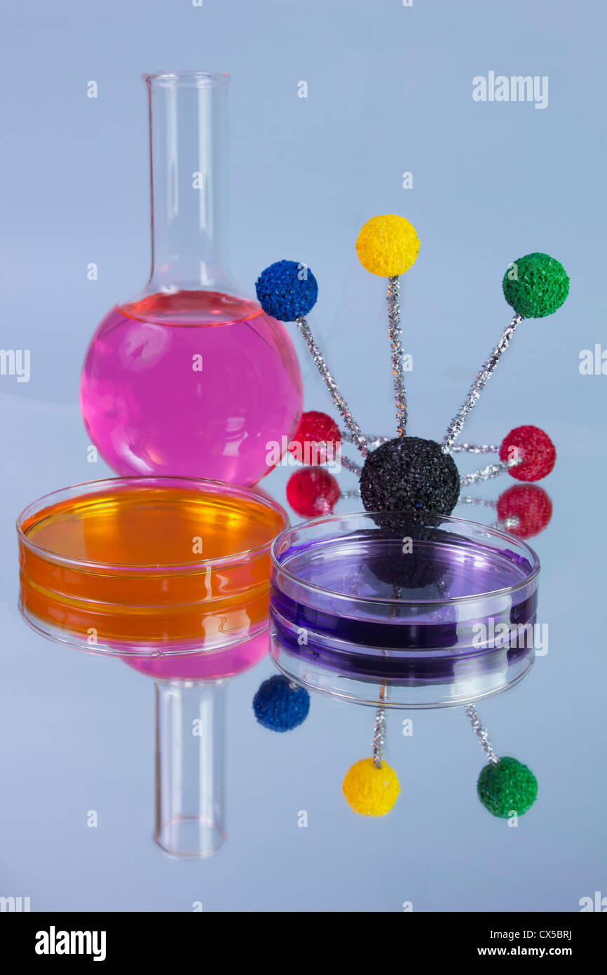 pink flask with orange and purple petri dishes and molecular model - Stock Image