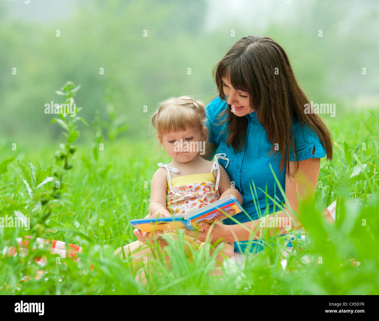 mother and daughter reading book together outdoor - Stock Image