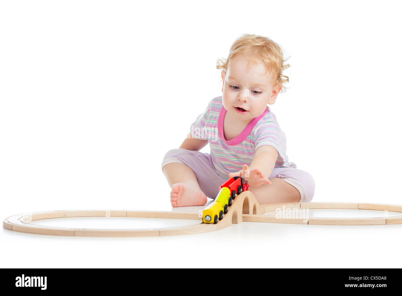 child is playing with wooden train isolated on white Stock Photo