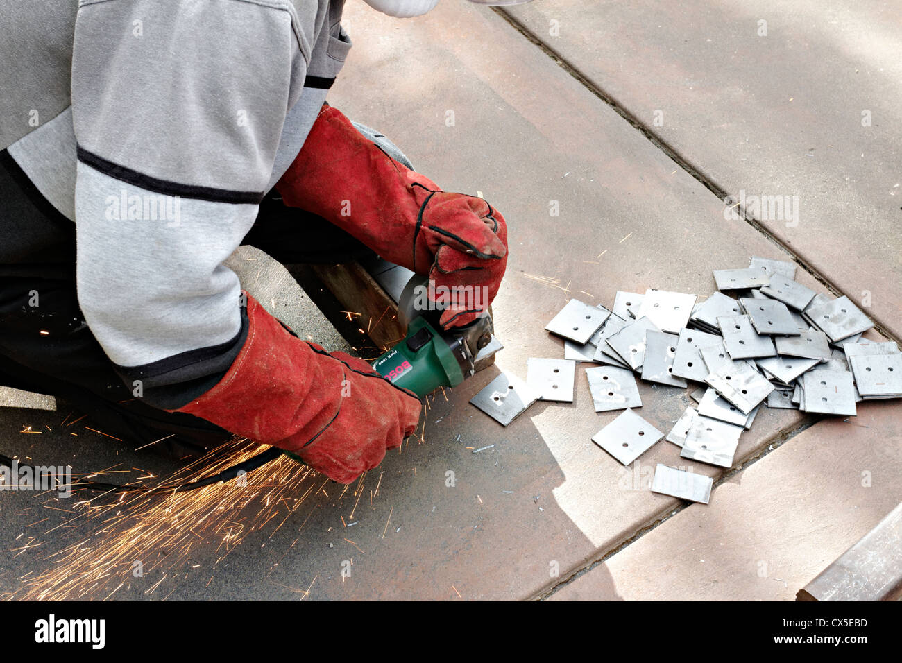 Man cutting metal with a angle grinder - Stock Image