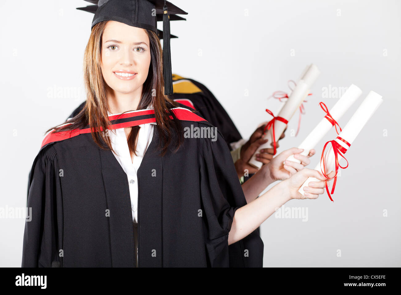 graduates holding diploma at graduation - Stock Image
