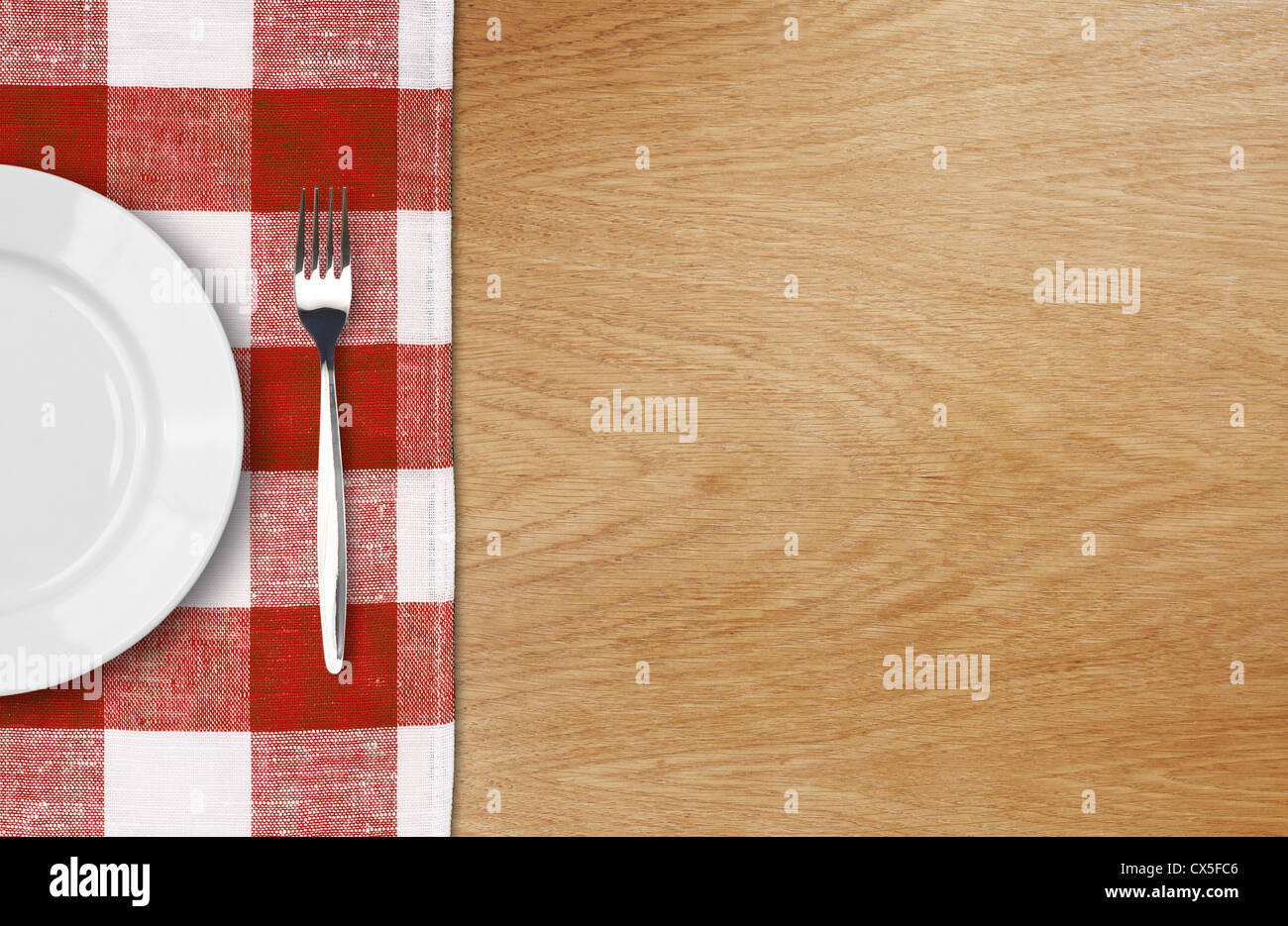 white plate and fork on wooden table with red checked tablecloth and copyspace - Stock Image