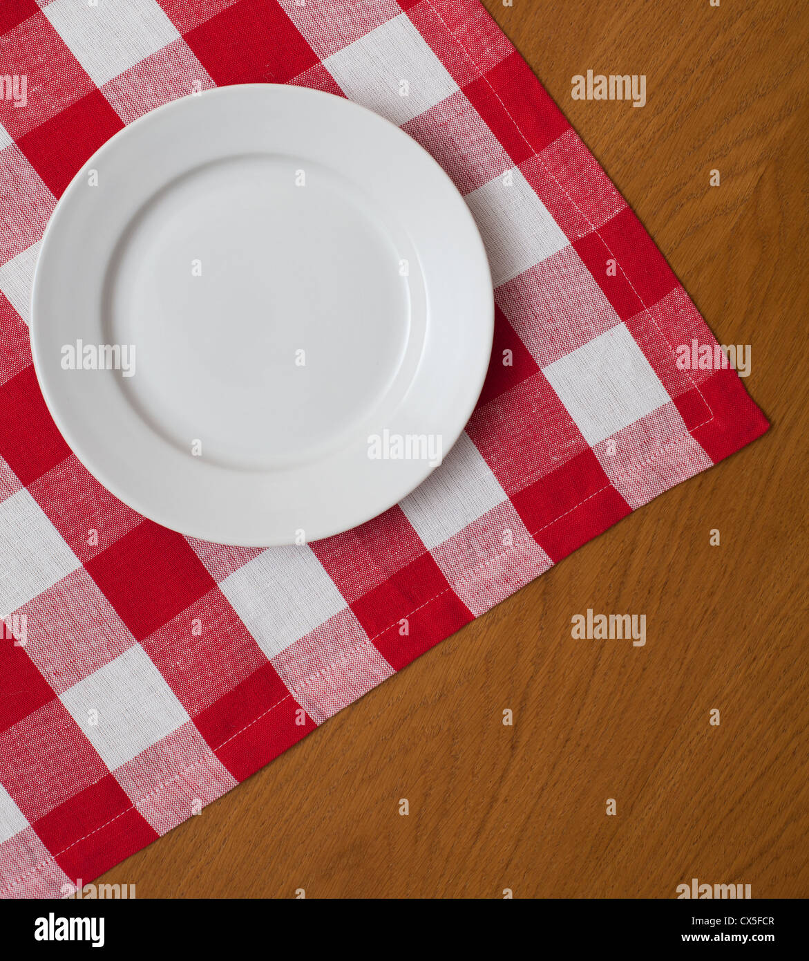 white plate on wooden table with red gingham tablecloth - Stock Image