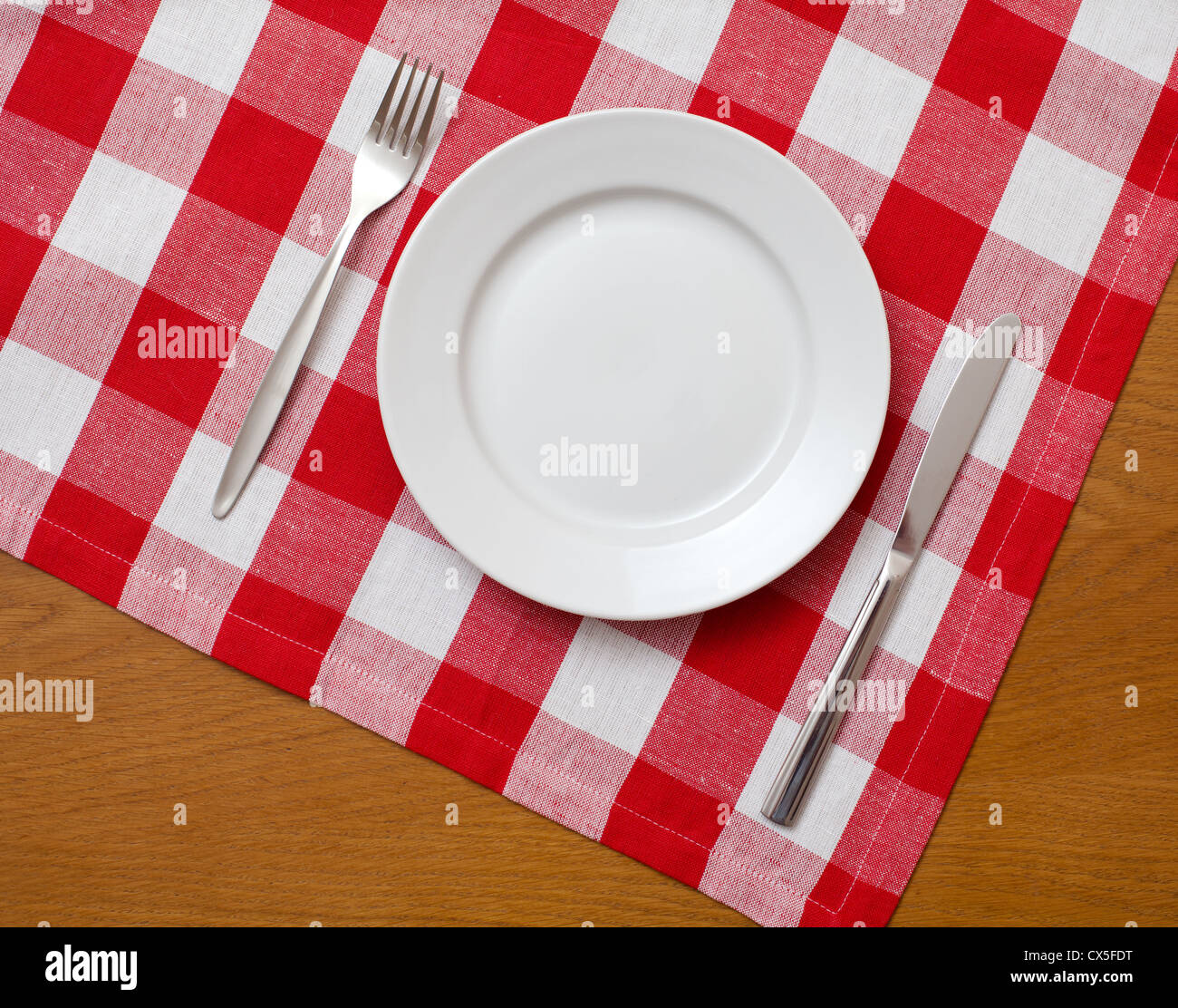 Knife, white plate and fork on wooden table with red checked tablecloth - Stock Image