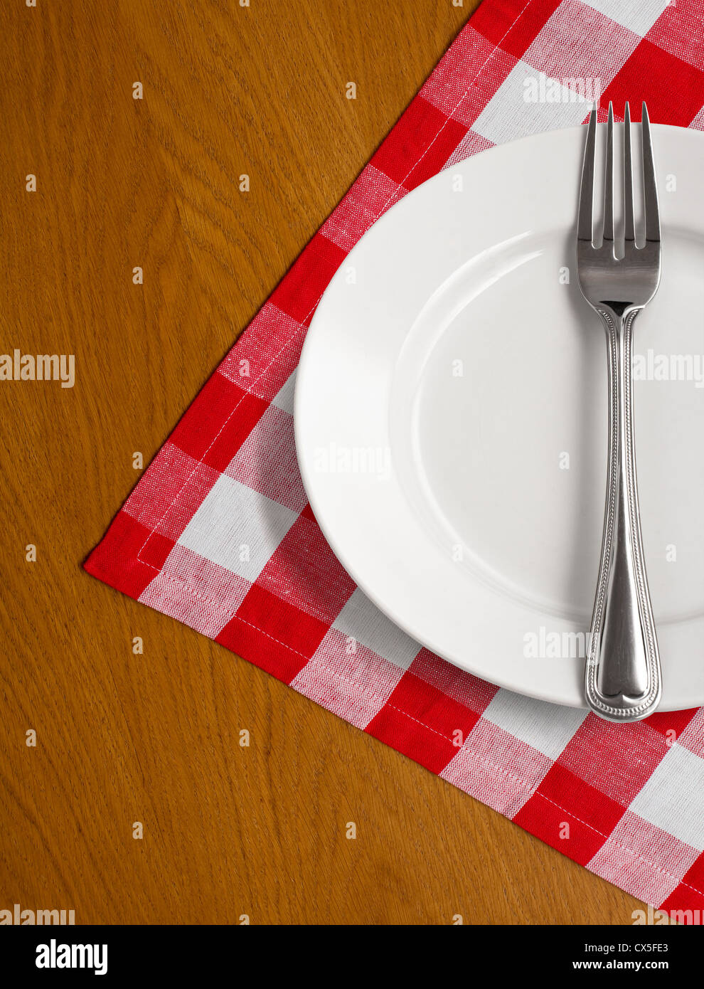 white plate and fork on wooden table with red checked tablecloth - Stock Image