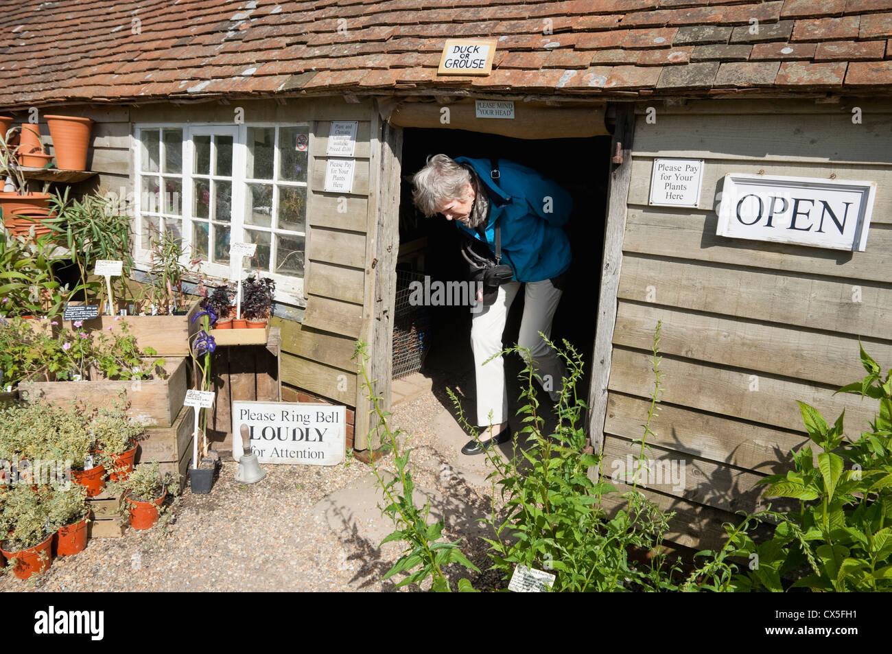 Nursery Plant Shop with low doorway and sign over saying 'Duck or Grouse' - at Great Dixter Garden, Sussex, - Stock Image