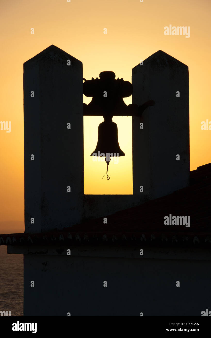 ALGARVE, PORTUGAL. A church campanile silhouetted against the setting sun. 2012. - Stock Image